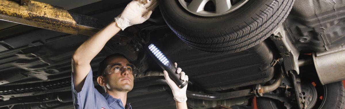 Hjulutrustningsreparatøren undersøker understellet på en bil.