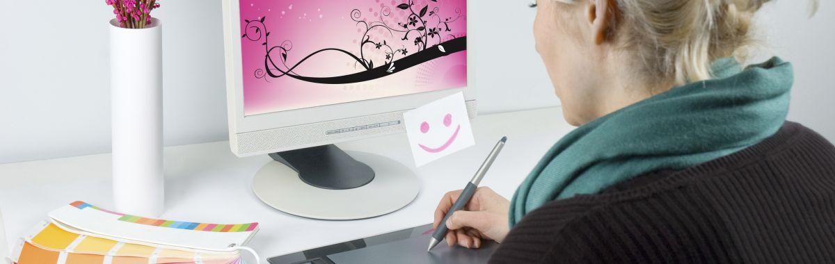 Mediegrafikeren sitter foran en dataskjerm og utarbeider grafikk.