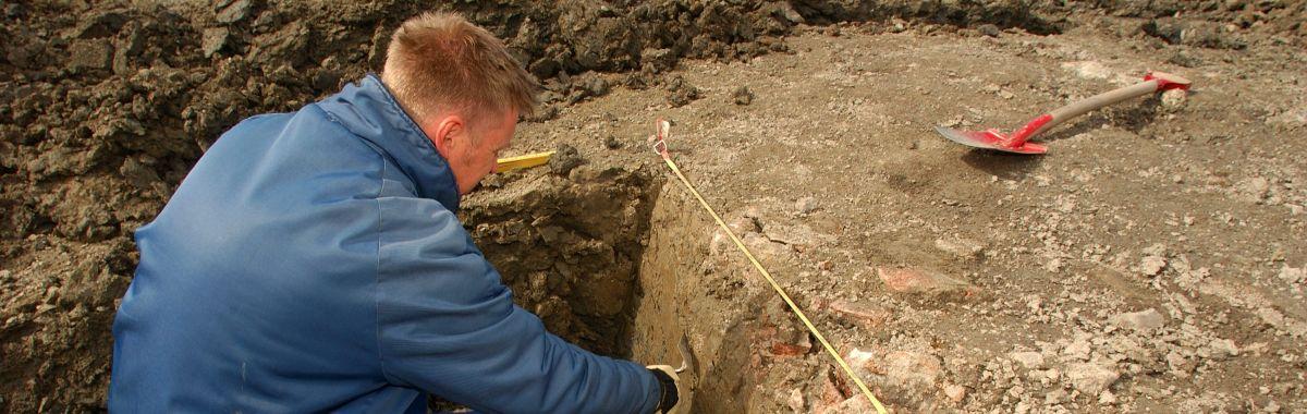 Arkeolog grev etter gamle boplasser i leire. Han bruker både lita skei og stor spade