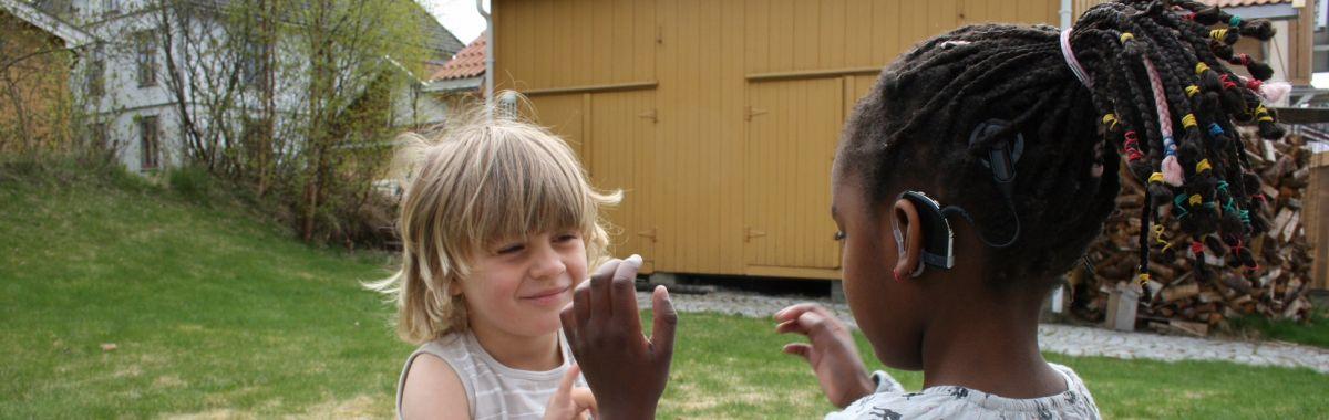 Illustrasjonsbilde av ei jente med cochlea implantat som leker med et annet barn.