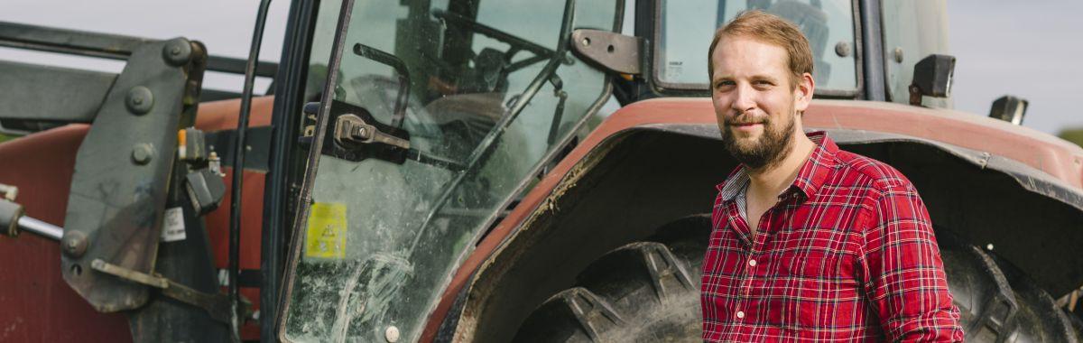 Avløser på gård foran traktor.