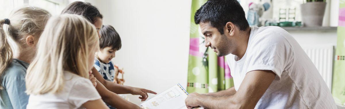 Barnehageassistent leser med barna.