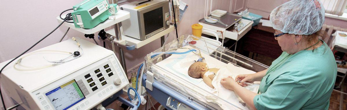 En kirurg ser til et for tidlig født barn i en inkubator. Inkubatorer brukes til for tidlig fødte (premature) barn, eller barn som er syke.