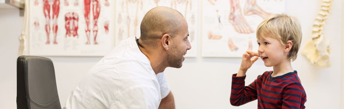 Mannlig lege prater med gutt som sitter på undersøkelsesbenk.