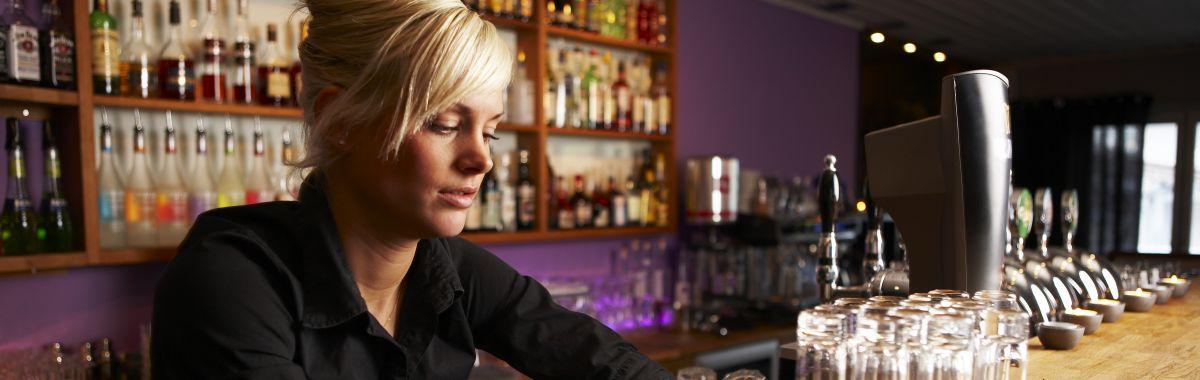 Ei ung dame står i en bar.