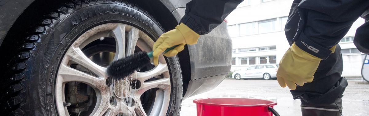 Bilklargjører vasker dekkene på en bil i Oslo.