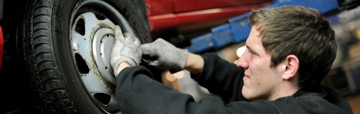 En ung mann jobber med et dekk på en bil.