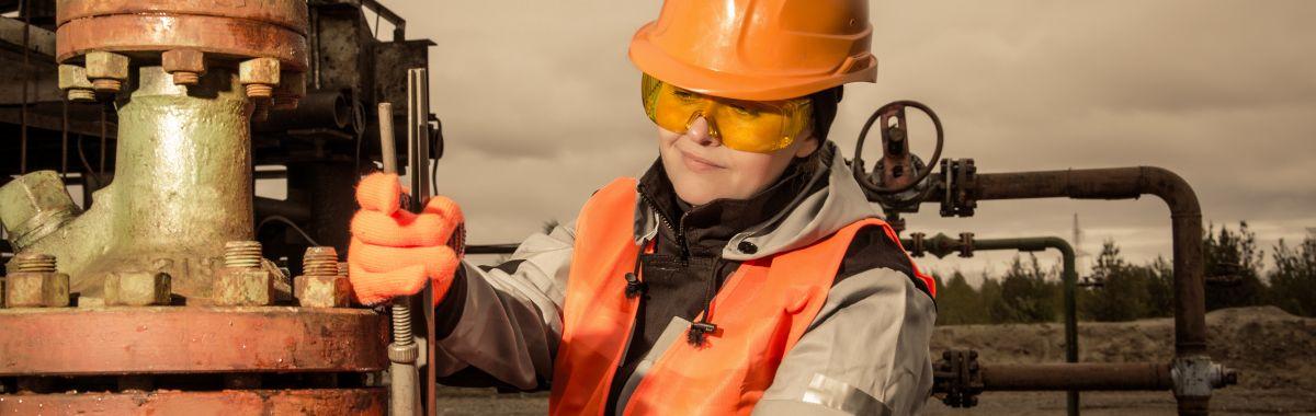 Kvinnelig brønnoperatør i arbeid på oljefelt.