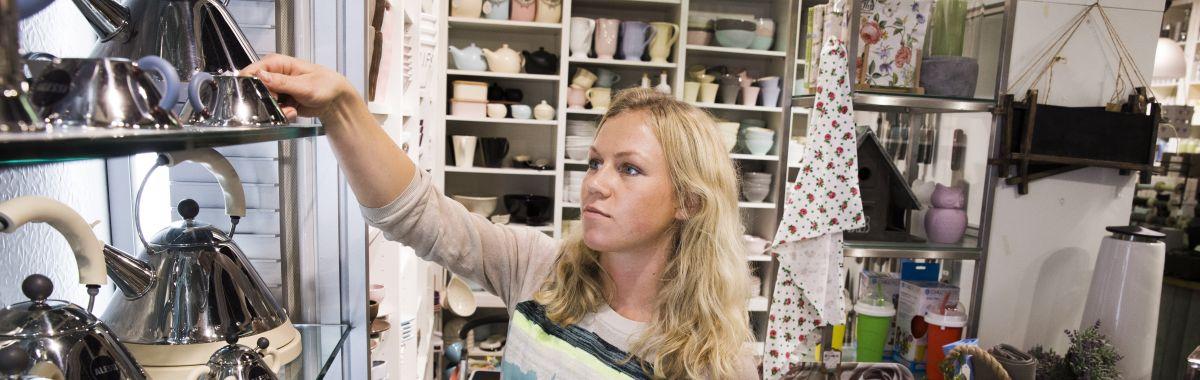 Illustrasjonsbilde av kvinne som står i en butikk og rydder i hyllene.
