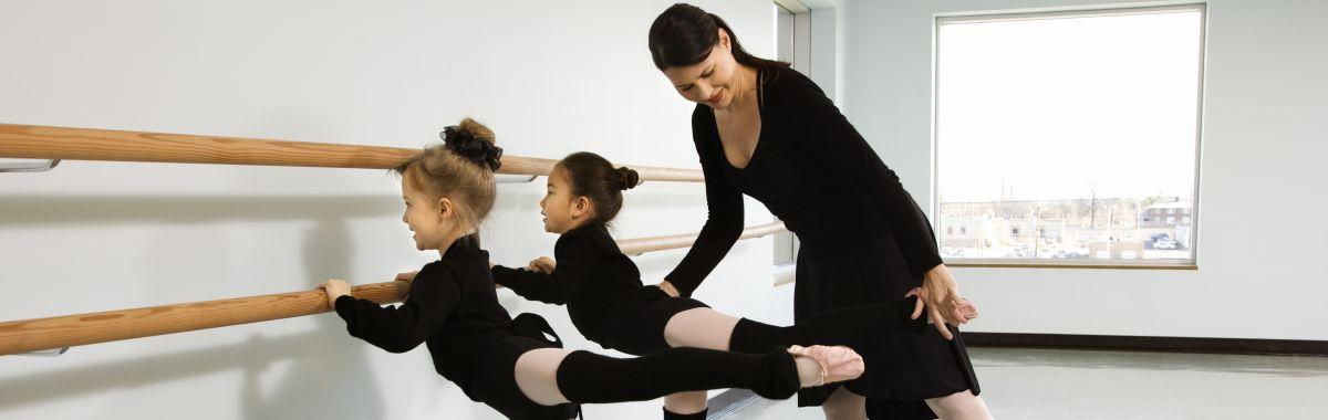 Ballettinstruktør hjelper to jenter med å utføre en arabesque.
