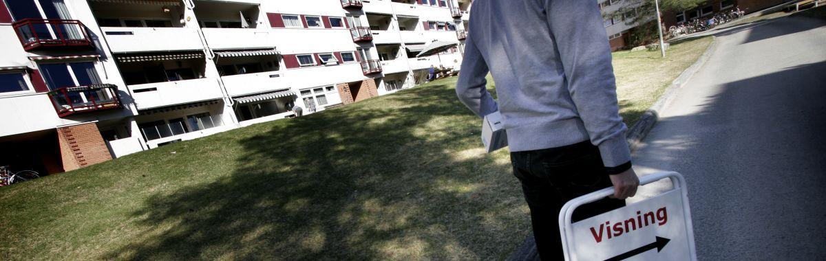 Eiendomsmegler bærer på et visningsskilt foran noen boligblokker