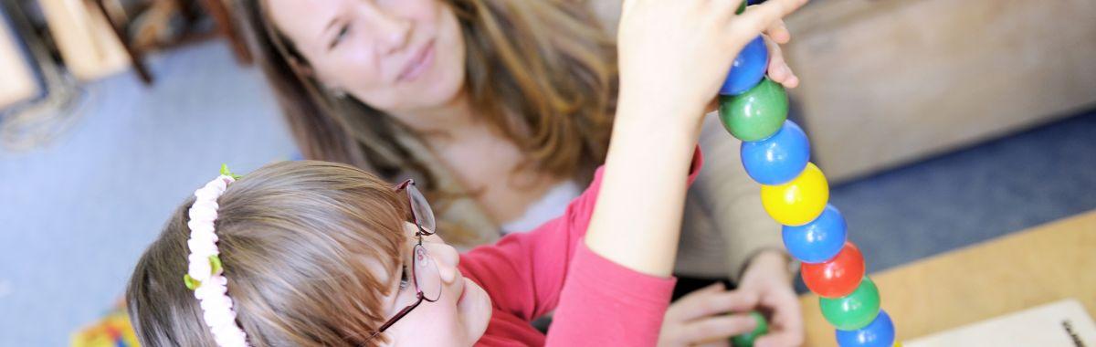 Jente stabler trekuler under oppsyn av kvinnelig ergoterapeut.