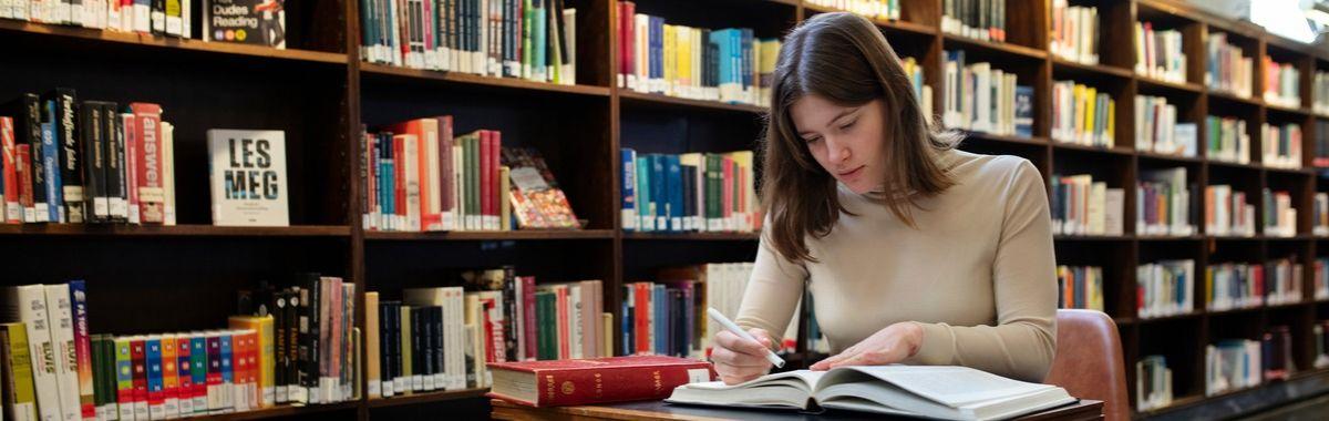 Filolog studerer en bok på et bibliotek
