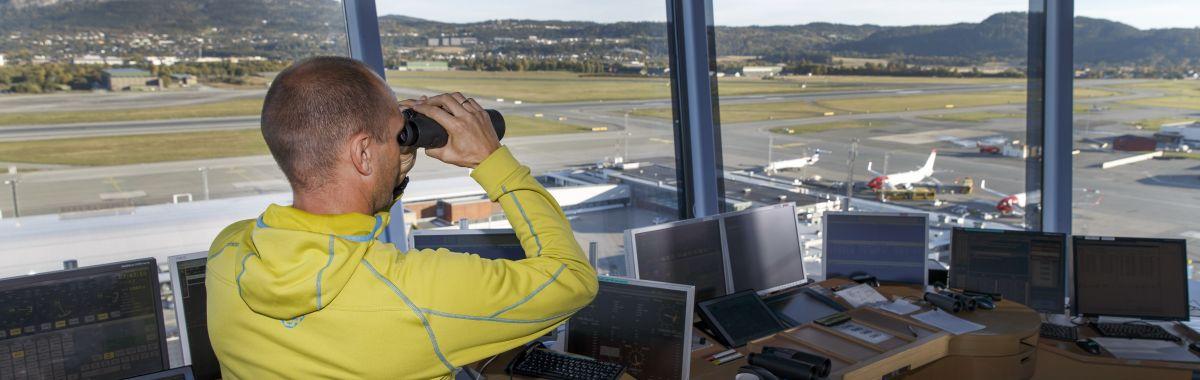 Flygeleiar på jobb i tårnet på ein flyplass.