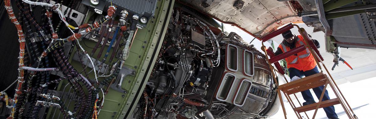 Flystrukturmekanikeren står i en stige og skrur på en motor på et passasjerfly.