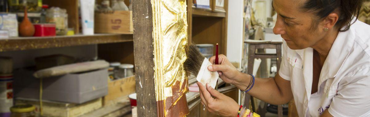 En dame sitter og forgyller et kunstverk på verkstedet sitt.