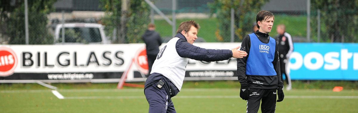 En fotballtrener gir instrukser til en fotballspiller.