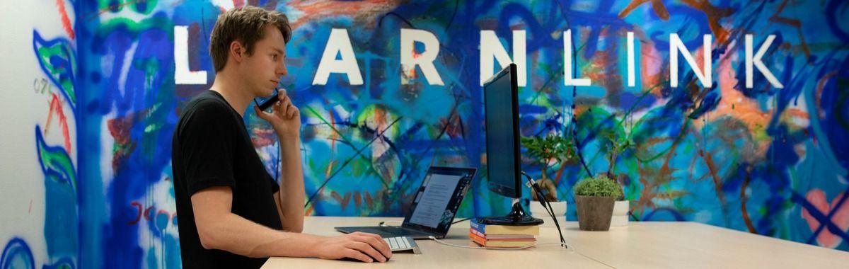 Gründer jobber på laptop samtidig som han snakker i telefon
