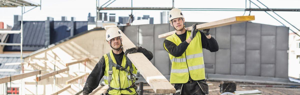 To arbeidere på byggeplass bærer materialer.