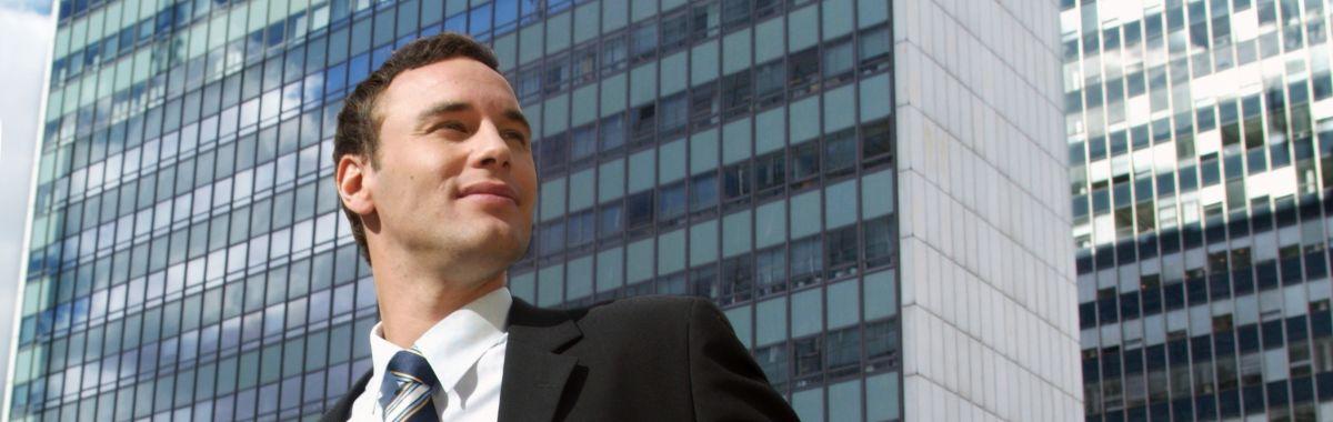 Mann i dress står utenfor en høy bygning.