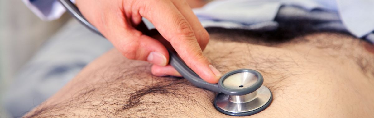 Eksaminasjon av indre organer i mageregion med stetoskop.