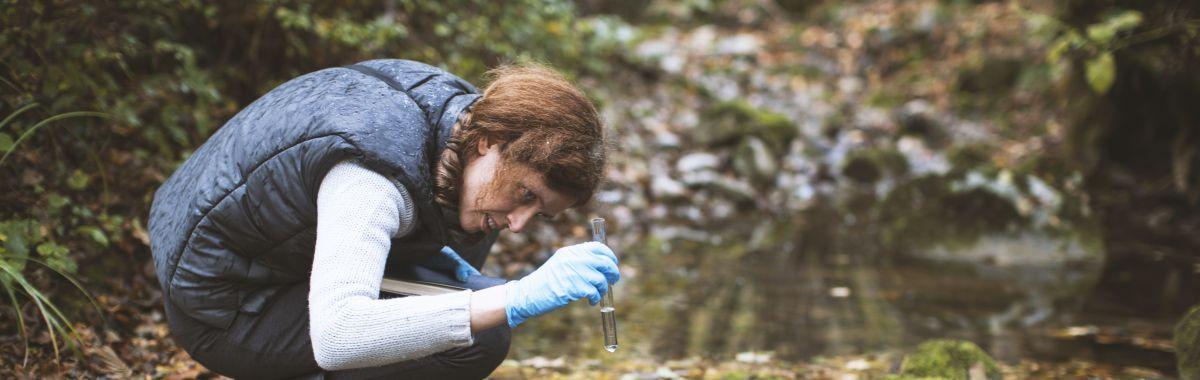 Kvinnelig biolog sitter på huk ved en bekk og ser på vannprøve i reagensglass