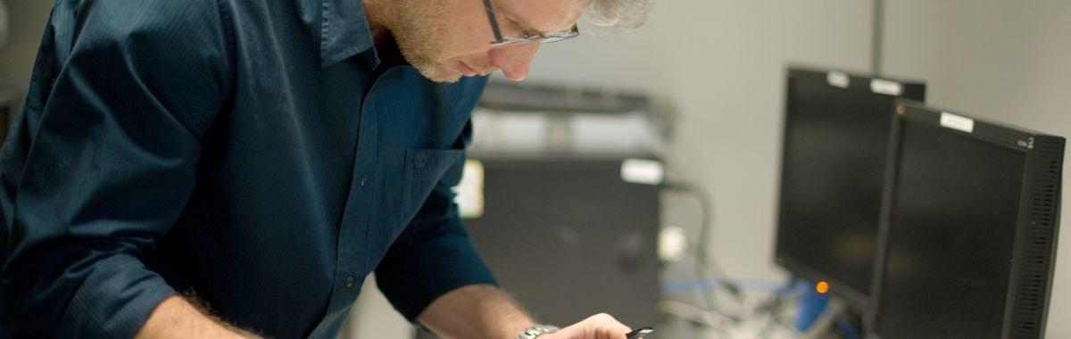 Ein mann reparerer en datamaskin.