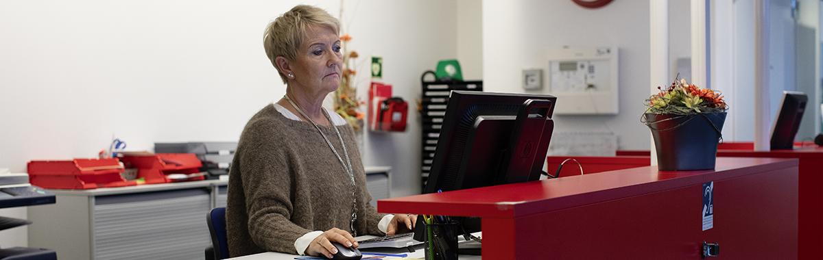 Kontor- og administrasjonsmedarbeider jobber foran PC