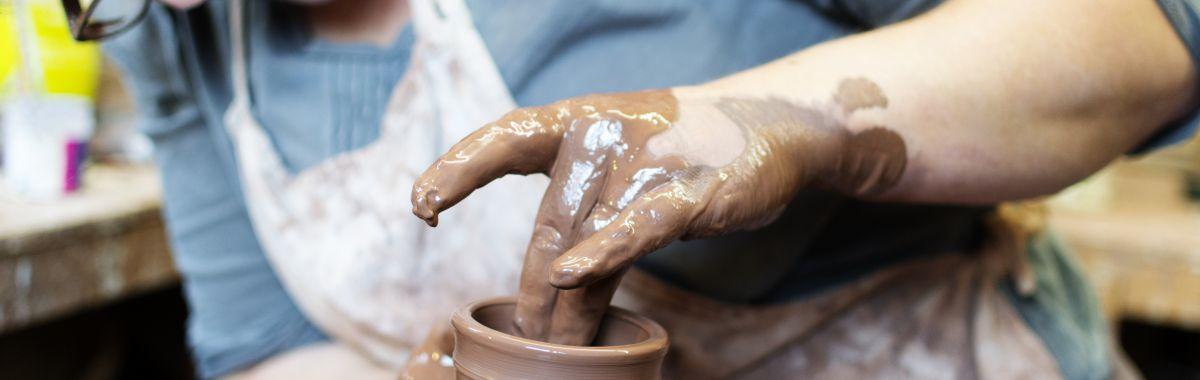Kvinnelig kunsthåndverker lager leirvase.