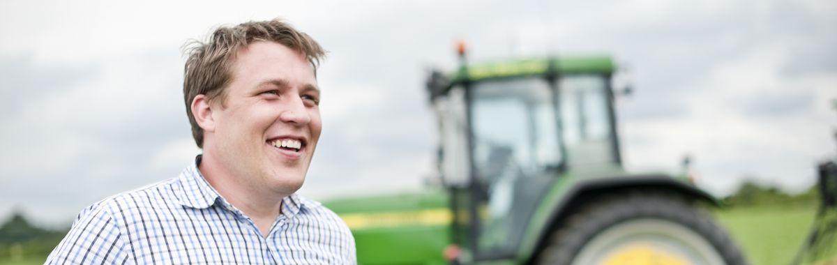 Mann står foran traktor.
