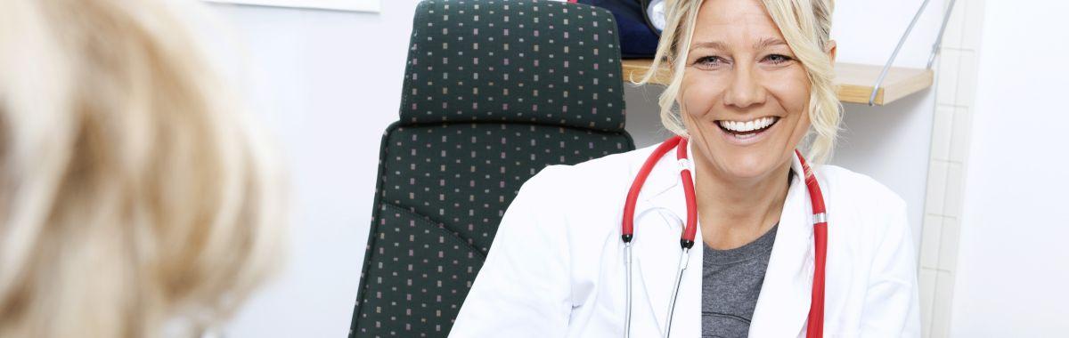 Kvinnelig lege smiler til pasient.