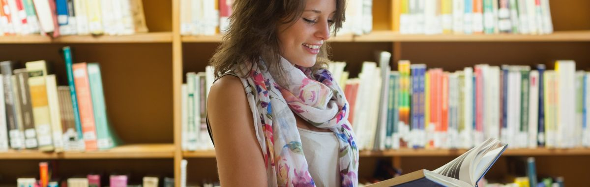 Kvinnelig litteraturviter leser bok i et bibliotek