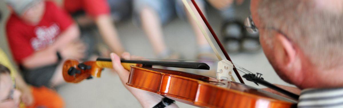 Musikkpedagog underviser elevene i å spille fiolin.