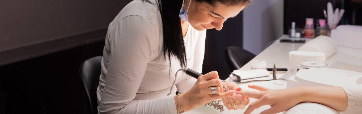 Negledesigner jobber med neglene til kunde.