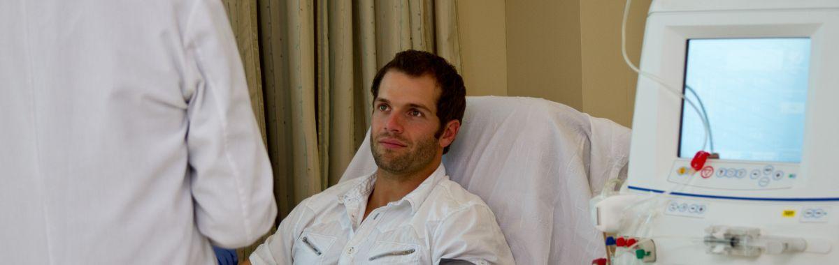 To leger og en pasient som mottar dialysebehandling.