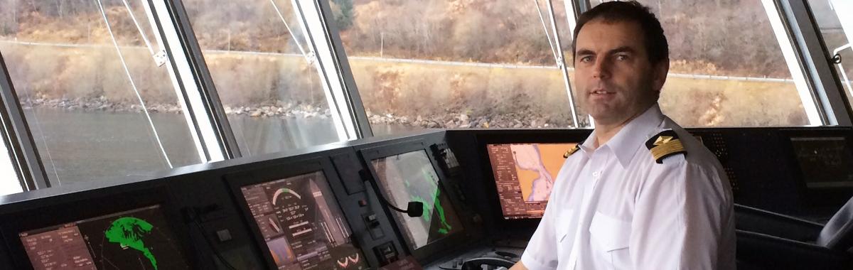 Overstyrmannen sitter ved kontrollpanelene på brua på et skip.