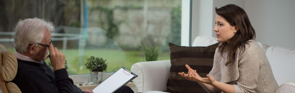 En mann sitter og lytter til dame som snakker.