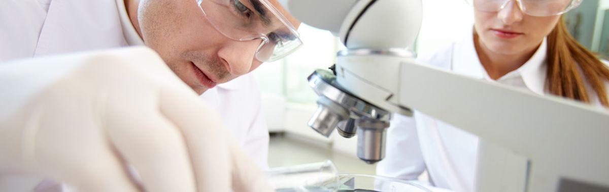 Mannlig og kvinnelig samfunnsmedisiner undersøker bakterier gjennom et mikroskop.