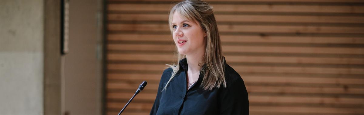 en kvinne i  snakker på en talerstol