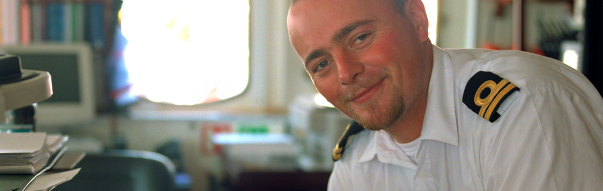 En styrmann i uniform jobber med navigering inne på dekk.