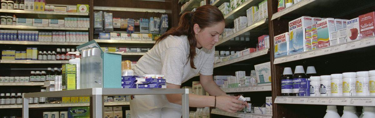 Kvinnelig apotektekniker legger varer i hyller
