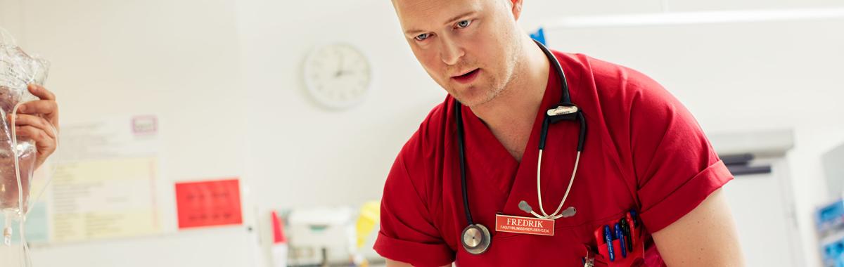 Sykepleier i rød uniform, stetoskop rundt halsen