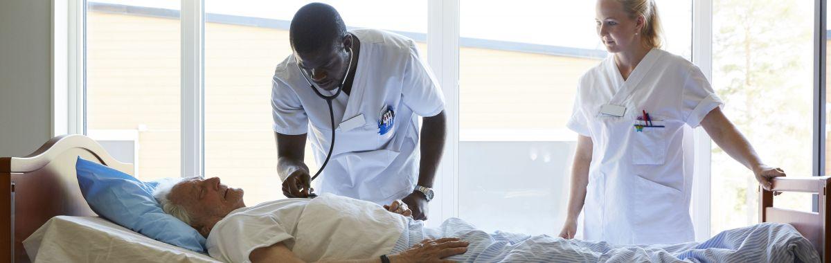 Mannlig sykepleier undersøker pasient mens kvinnelig sykepleier står ved siden av og ser på.