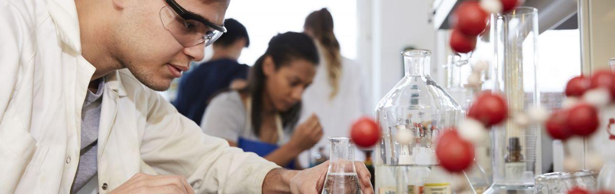 Mannlig biokjemiker studerer kjemikalie i glassflaske