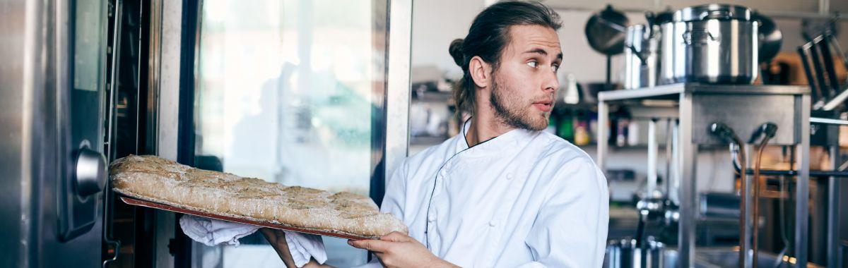 Ung mannlig baker setter bakverk i ovnen