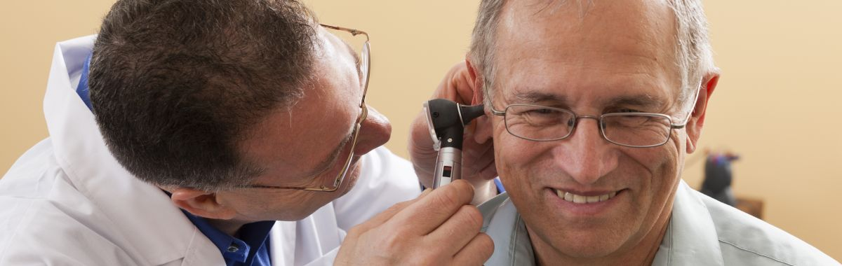 A doctor looks in a patient´s ear.