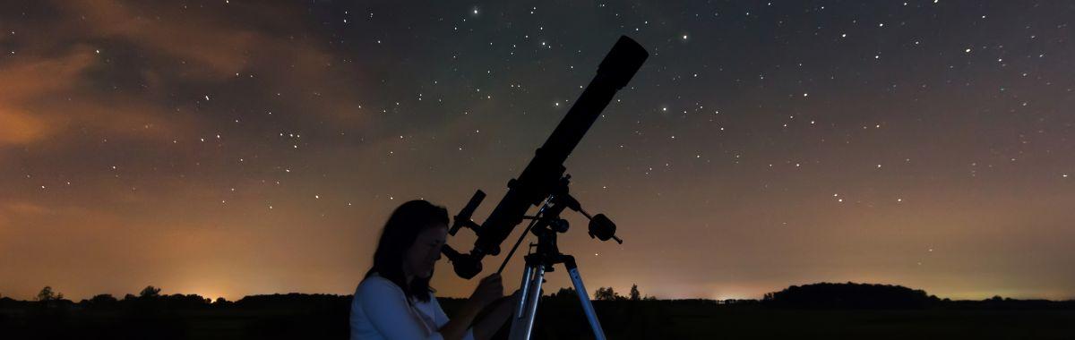 En astronom kikker på stjernene på nattehimmelen.