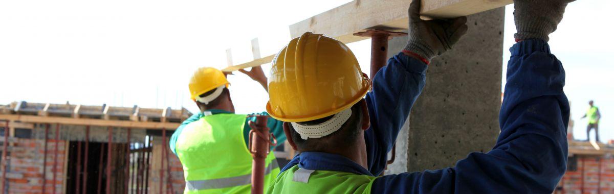 To tømrere på en byggeplass støtter en planke.