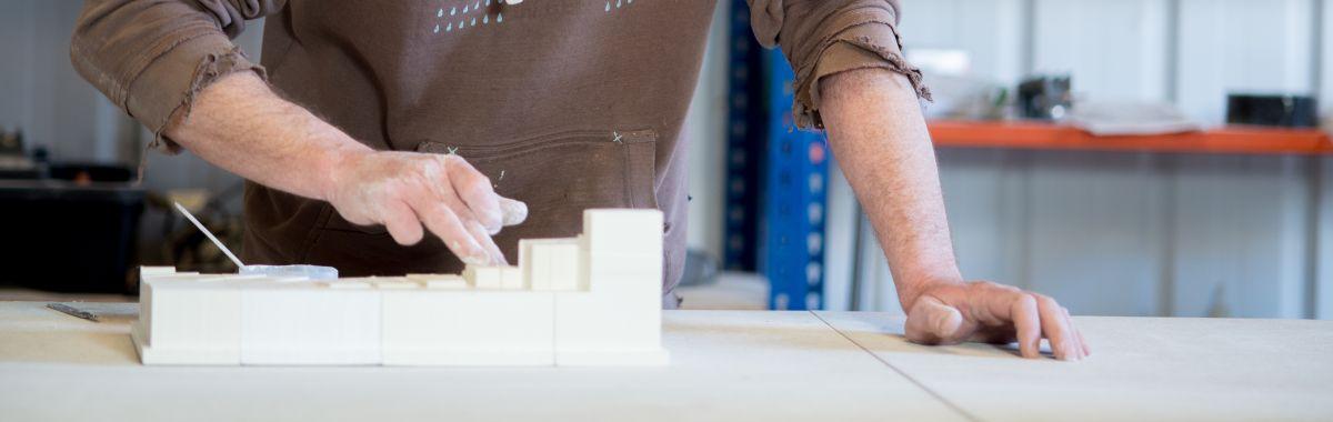 Utstillingsdesigner smører hvit maling på gipsmodell.
